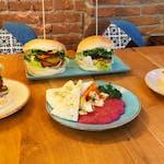 Przystawka: 🥗 Hummus buraczany z marynowanym tofu, chrupiącymi warzywami i domową pitą , 🍔 Obeliks - placek ziemniaczany, tofu wędzone, sałata, cebula, ogórek, sos BBQ i czosnkowy, 🍰 Tofurnik z polewą czekoladową