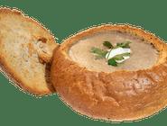 Krem z grzybów leśnych podany w czarce chlebowej, z dodatkiem śmietany, grzanek i natki pietruszki