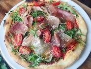 Pizza na cienkim cieście z Szynka parmeńską, serem dojrzewającym, rukolą, pomiodorkami, i oliwą