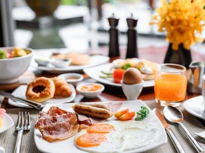Jajecznica na maśle, frankfurterki lub parówki lub omlet,, jajka gotowane lub sadzone, wędliny, pasty, ser żółty, pomidor, ogórek pieczywo mieszane, masełko, dżem, miód, kawa, herbaty, pełna zastawa